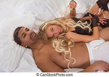 young interracial couple in sexual games on bed - Playful...