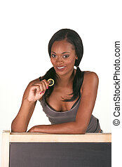 African-American woman with condom by blackboard - Young...