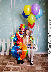 Little girl with the clown shake on a swing.