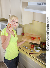 Young blond woman with vegetables on kitchen - Caucasian...