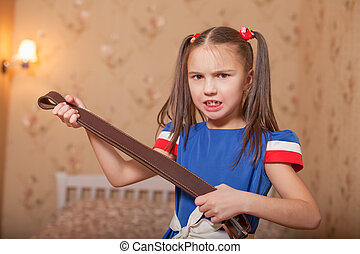 Angry little girl with belt in hand.