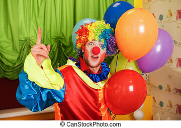 Funny clown with a bunch of colorful air balloons standing...