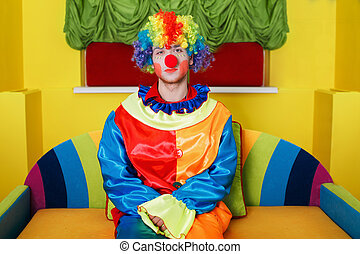 Clown sitting on colorful sofa. - Clown in rainbow colored...