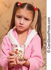 Little girl with glass full of tablets.