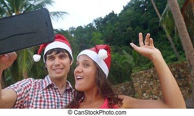 Happy beautiful couple on Christmas travel holidays taking...