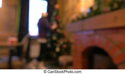 Blurred young woman decorating Christmas tree. 4K background...