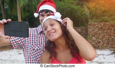 Happy couple on Christmas travel holidays taking selfie...