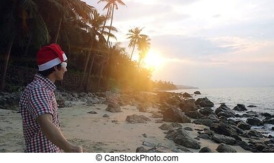 Handsome man wearing Christmas hat enjoying on Christmas travel holidays at sunset in slow motion.