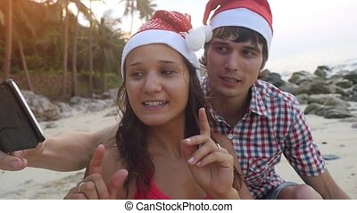 Happy beautiful couple on Christmas travel holidays taking...
