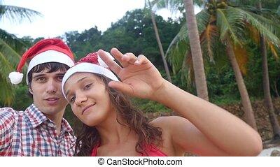 Happy joyful couple on Christmas travel holidays taking...