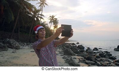 Handsome man wearing Santa's hat on Christmas travel holidays takes selfies and having video chat using smartphone on tropical beach at sunset in slow motion.