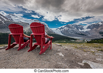 Behind View of Two People Sitting in Red Chairs on Trail