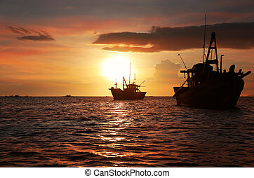 Silhouettes of anchored fishing boats - Dark silhouettes of...