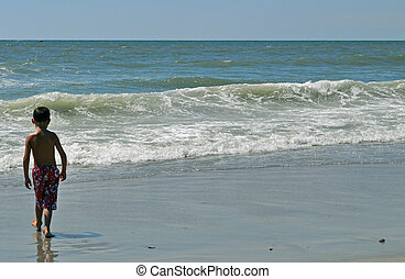 Boy walks toward the waves