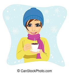 young woman wearing winter clothes having cup of hot...