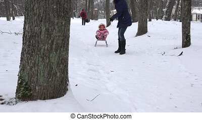 woman pull baby child on sledge through snow in park tree alley. 4K