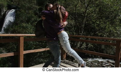 Lovers man and woman whirling and kissing at forest near...