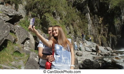 Couple taking selfie picture of waterfall - Selfie couple...