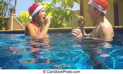 Happy joyful couple dives under water in the pool in Santa...
