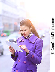 young woman with tablet in the street