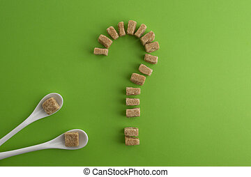 Brown sugar cubes shaped as a question mark on greenery...