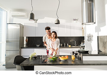 Young Couple Embrace In Kitchen, Hispanic Man And Asian...