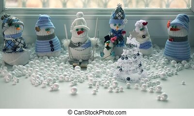 Toy handmade snowmen on a windowsill and snowstorm outside...