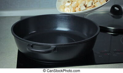 Cook puts the mushrooms to the frying pan and ready to fry