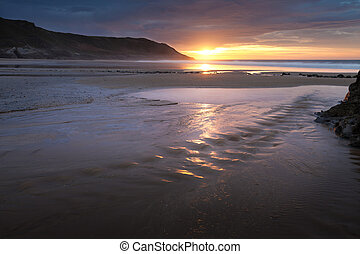Caswell Bay beach stream - Sunrise over a beach stream at...