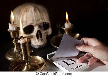 Friday 13th on a calendar with candles and a creepy skull