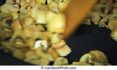 Mushrooms fried with oil in a frying pan. Cook stirs...