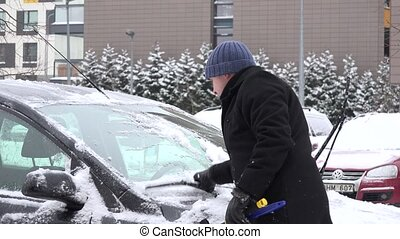 Man clean snow from car windshield after heavy snowfall. 4K...