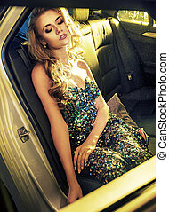 Tired blond lady sitting in the limo