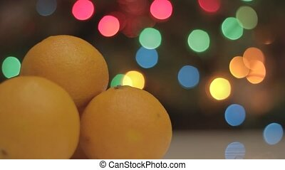 Bright yellow mandarins on the Christmas tree with garland