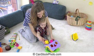 young loving mom teaches daughter girl to distinguish object...