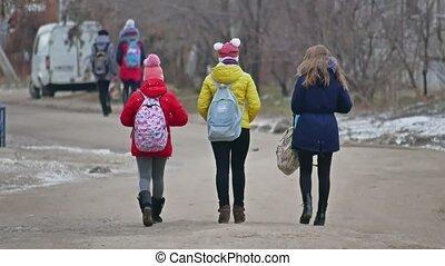 Winter children go to school, school girl with backpack goes...