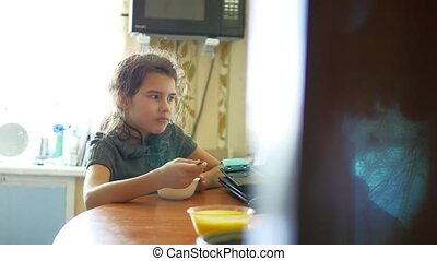 Teen girl eating cereal in the kitchen school girl with a...