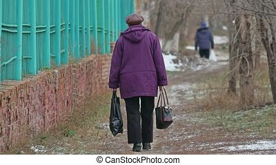 old woman is limping down the street, bears a bag and a...