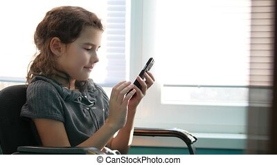 teen girl sitting by the window with smartphone playing...