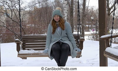 Young beautiful model, riding on a swing in the park. In...