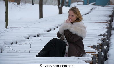 Beautiful young model hand warms. Very cold, winter, snow,...