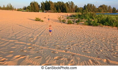 Small Girl Runs Barefooted on Sand Dunes to Mother at Sunset...