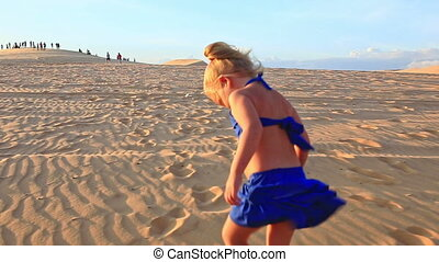Small Girl Walks Barefooted on Sand Dunes Stops Tired at...