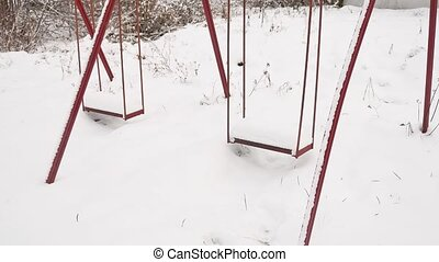 old swing at the playground in the winter snow - old swing...