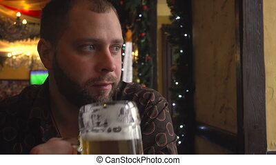 Man with beard drinking beer in pub from big glass and enjoy...