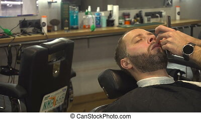 Barberman shaving beard of man - Barberman in barber shop...