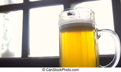 Full glass of fresh golden beer in pub