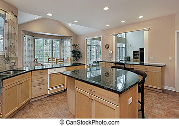 Kitchen with marble top island - Kitchen in luxury home with...