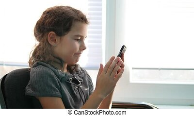 teen girl sitting by the window smartphone playing online...