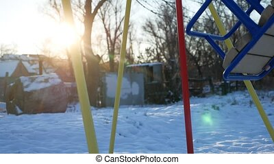 swing for children swinging on the playground snow winter...